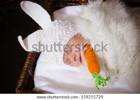 the sleeping baby in a suit of a rabbit with carrot - stock photo