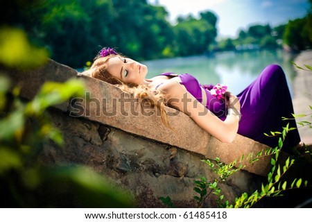 The sleeping beauty lays on stones near to the river - stock photo