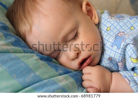 The sleeping small, beautiful boy laying on a sofa with an open mouth