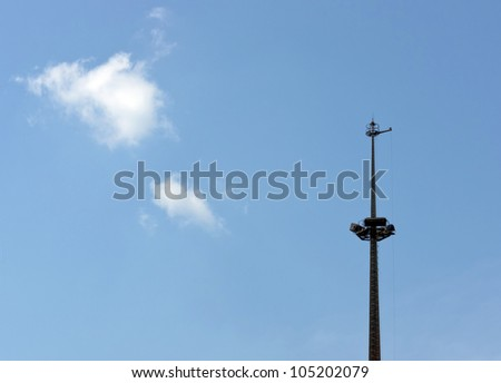 The slender spire and white cloud in the blue sky