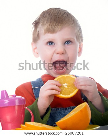 The small beautiful boy eats an orange