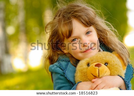 The small beautiful girl embraces an amusing bear cub against summer nature.