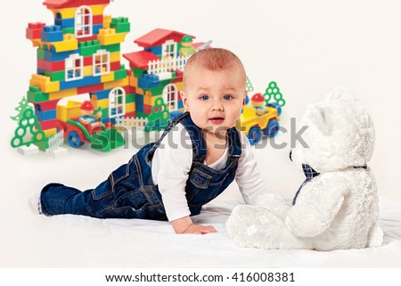 the small boy in blue overalls plays with a teddy bear - stock photo