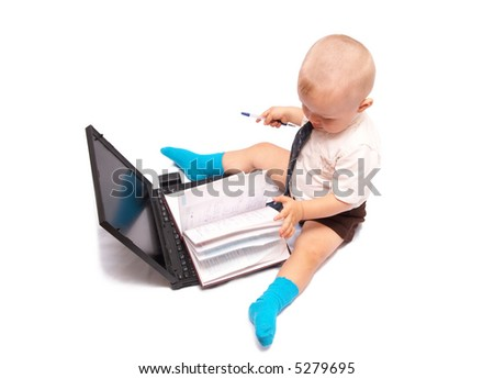 The small boy sits with the computer on a white background