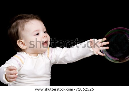 The small child and soap bubbles against a dark background