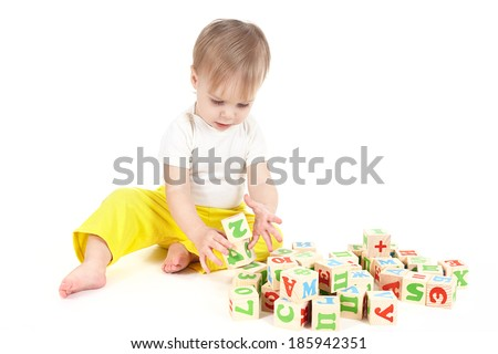 The small child builds a tower of cubes - stock photo
