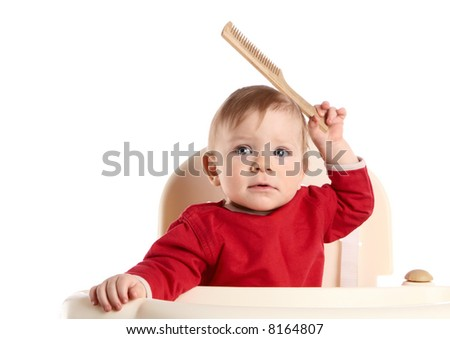The small child holds a hairbrush in a hand - stock photo