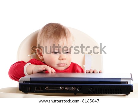 The small child tries to open laptop - stock photo