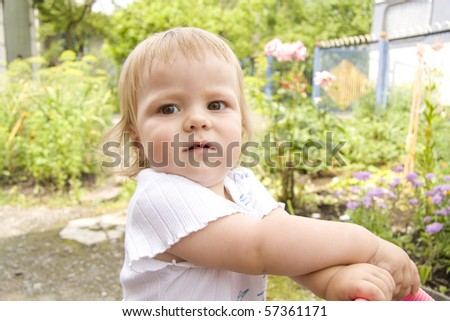 The small child walks with a children's carriage in the summer in a garden and distracts