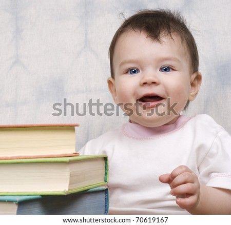 The small child with books on a light background