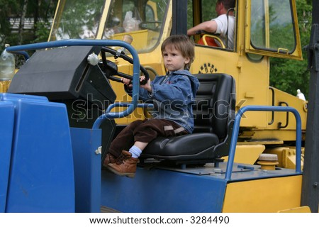 The small child would like to play with greater toys and to look as the present adult worker - stock photo
