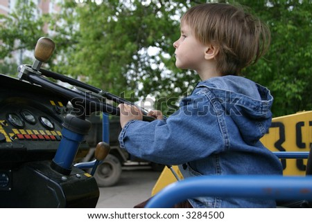 The small child would like to play with real road roller and want to look as the adult worker - stock photo