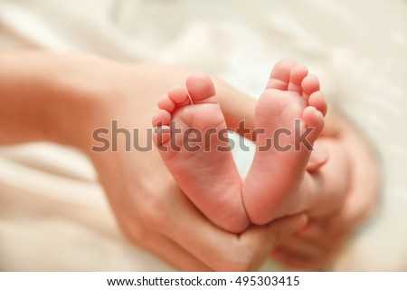 The Small Cute Soles of Newborn Feet are in the Father's Hands.