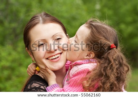 The small daughter kisses mum - stock photo
