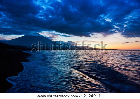 The small fishing village of Amed, Bali is dwarfed by the active volcano Gunung Agung which last erupted in 1962. The beach is of the black sand variety. - stock photo