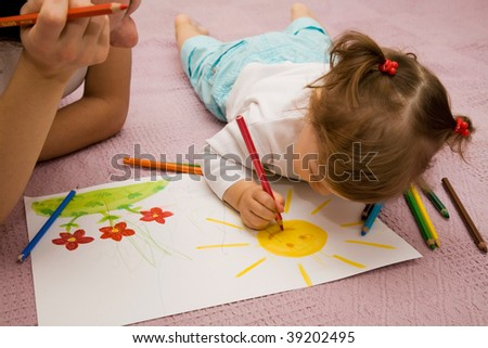 The small girl draws pencils with mother lying on a floor
