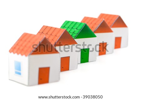 The small green house among red houses on a white background. A real estate choice. Selective focus - stock photo