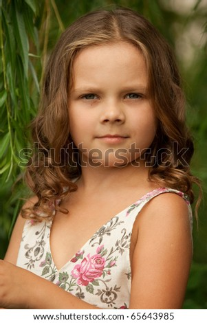 The small lovely girl with a flowing hair, at nature background.