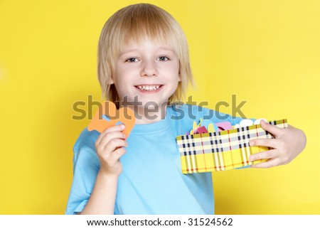 The small schoolboy with letters on a yellow background - stock photo