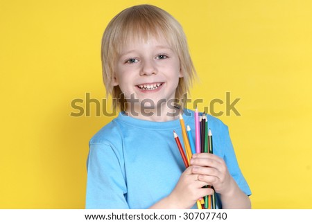 The small schoolboy with pencils on a yellow background - stock photo