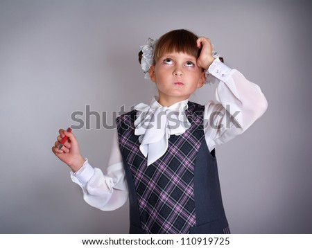 The small schoolgirl in a gray dress thinks over the solution of a task - stock photo