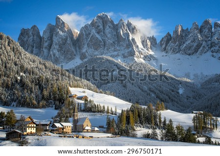 The small village of St. Magdalena or Santa Maddalena with its church covered in snow and with the Odle or Geisler Dolomites mountains in the Val di Funes Valley in South Tyrol in Italy in winter.