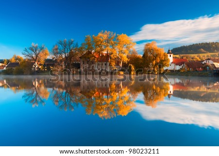 The small village standing near the pond - stock photo