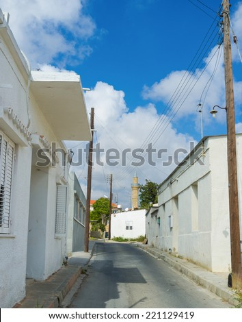 The small white houses with the minaret of the Moutallos Mosque on the background, Paphos, Cyprus.