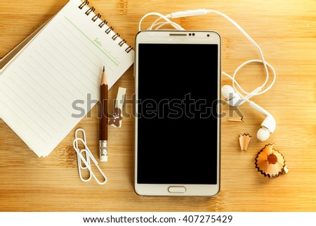 The Smart phone with Blank notepad and  pencil  on wooden table , overhead shot or Top view - stock photo