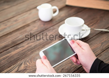 The smartphone and cup of coffee on an old wooden table - stock photo
