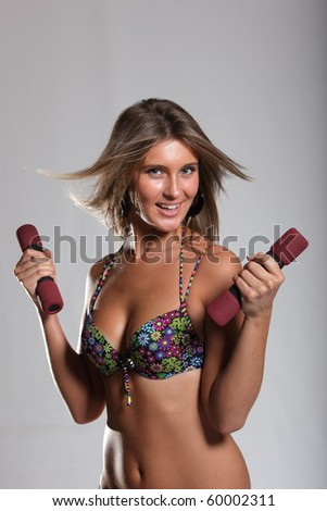 The smile girl in bikini with dumbbells in hands