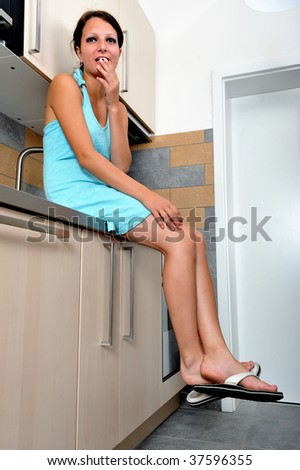 The Smile on her face: Beautiful young brunette sitting on a kitchen unit and smilling