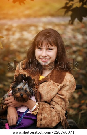 the smiling cheerful girl on a wheelchair with the dog in autumn - stock photo
