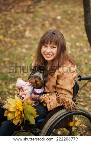 the smiling cheerful girl on a wheelchair with the dog in autumn forest - stock photo