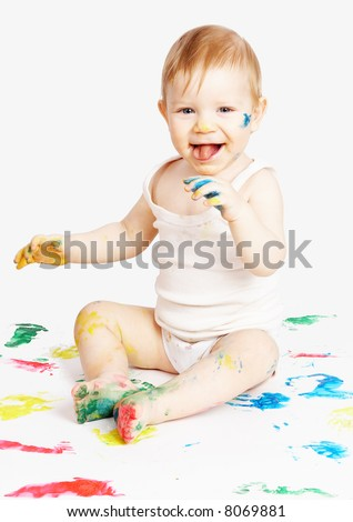 The smiling child sits among traces from water paints - stock photo