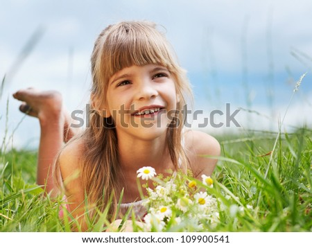 The smiling girl is lying in the green meadow - stock photo
