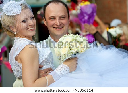 The smiling groom carrying a happy bride in his arms; wedding day - stock photo