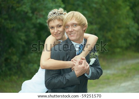 The smiling happy bride embraces the groom - stock photo