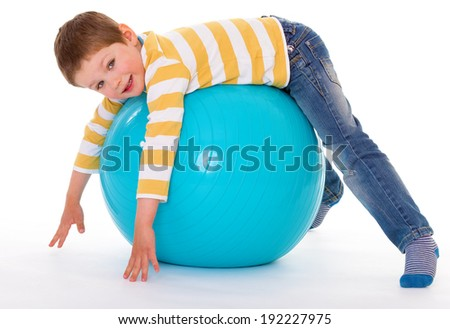 The smiling little boy is lying on his stomach on the big blue ball, isolated on white background - stock photo