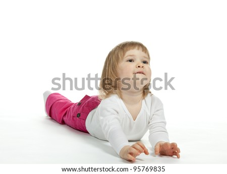 The smiling little girl lying on the floor; white background
