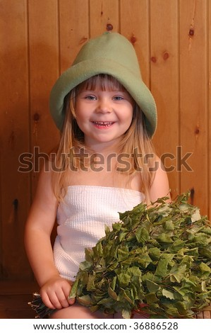 The smiling little girl with a broom in a sauna - stock photo