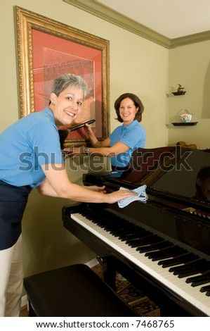 The smiling maids (housekeeping staff) in blue uniforms with aprons. One with a feather duster dusting a picture and the other with a dust cloth polishing a baby grand piano.