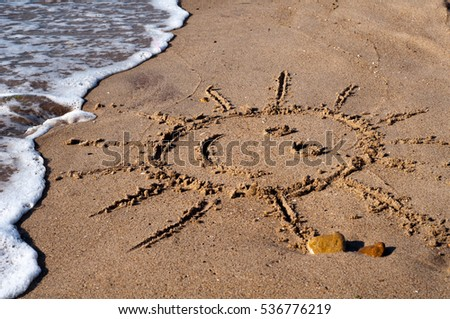 The smiling sun drawn in the sand. Summer rest