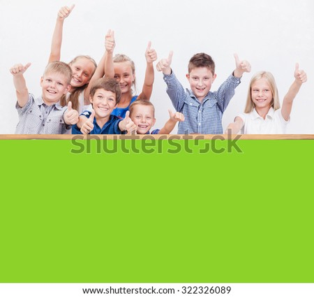 The smiling teenagers showing okay sign on white background and  empty green blank or copyspace .  - stock photo
