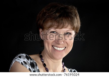 The smiling woman of average years on a black background - stock photo