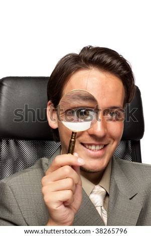 The smiling young businessman with a magnifying glass on a white background.