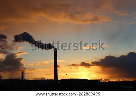 the smoke from the chimney of the power plant at sunset