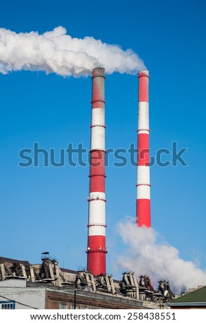 The smoke from the chimneys against the blue sky - stock photo