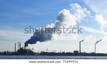 The smoke goes from factory's pipes in the snow field - stock photo