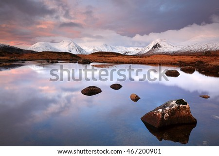 The snow covered Blackmount mountain range and Lochan at Glencoe during a colourful Sunrise.